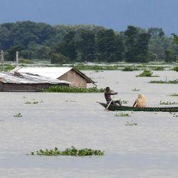 Los aldeanos viajan en un bote en la zona afectada por las inundaciones de la aldea de Gagalmari en el distrito de Morigaon del estado de Assam. | Foto:Biju Boro / AFP