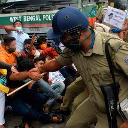 El personal policial se enfrenta con activistas del Partido Bharatiya Janata mientras gritan consignas y protestan durante una huelga que exige al Buró Central de Investigación (CBI) una investigación sobre la muerte de BJP MLA Debendra Nath Roy en Hemtabad, en Siliguri. | Foto:DIPTENDU DUTTA / AFP