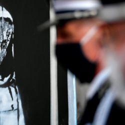 Policías italianos y franceses se paran junto a la obra de arte del artista callejero Banksy, en conmemoración de las víctimas de los ataques terroristas de París en 2015 que fueron robados de la sala de conciertos Bataclan en 2019 y encontrados más tarde en Italia, durante una ceremonia para devolver la obra a Francia, en la embajada de Francia en el Palacio Farnese, en Roma. | Foto:Filippo Monteforte / AFP)