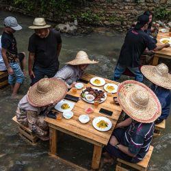 Los clientes almuerzan en un restaurante con mesas en la corriente de un río en Kampung Kemensah, en las afueras de Kuala Lumpur. | Foto:Mohd Rasfan / AFP