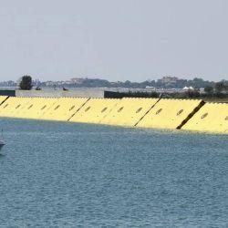 El proyecto consta de 78 barreras móviles de color amarillo enterradas en el agua.