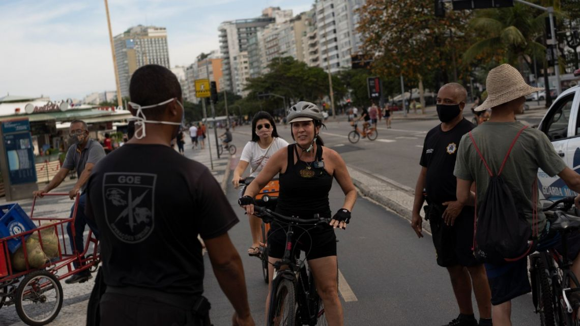 A municipal guard stops a woman on a bike to tell her to wear a mask at Copacabana beach amid the outbreak of the new coronavirus in Rio de Janeiro, Brazil, Sunday, July 12, 2020.