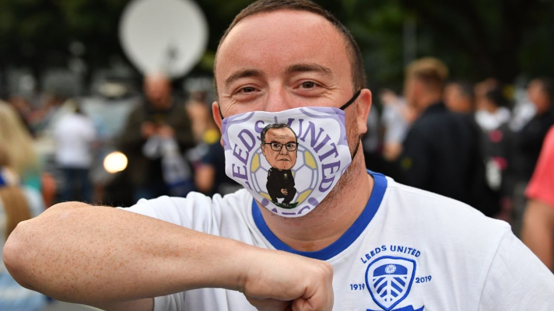 A supporter wearing a Leeds face covering gestures outside their Elland Road ground as fans celebrate the club's return to the Premier League after a gap of 16 years, in Leeds, northern England on July 17, 2020.