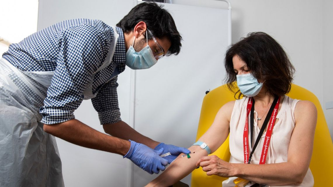 In this handout photo released by the University of Oxford a doctor takes blood samples for use in a coronavirus vaccine trial in Oxford, England, Thursday June 25, 2020.