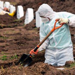 Los trabajadores que usan equipos de bioseguridad preparan tumbas para presuntas víctimas del nuevo coronavirus Covid-19, en el cementerio de San Diego, en el Centro Colonial de Quito. | Foto:Cristina Vega Rhor / AFP