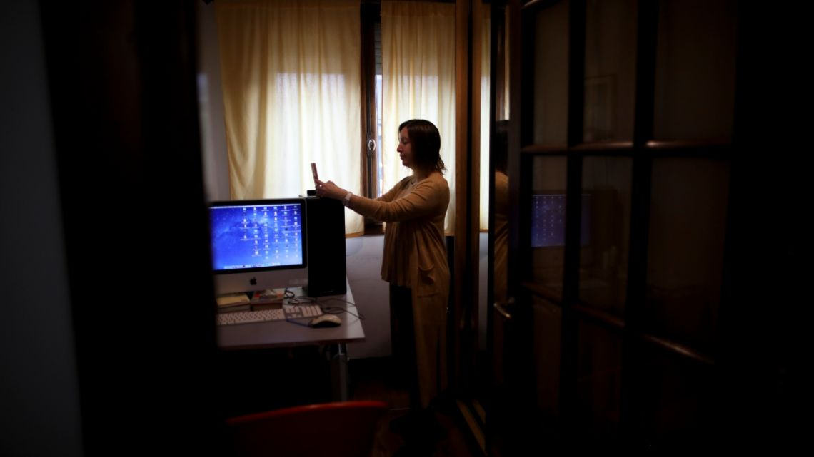 Psychologist Maria Clara Benitez text messages in the room where she attends patients online at her home during a government-ordered lockdown to curb the spread of the new coronavirus in Buenos Aires, Argentina, Monday, July 20, 2020.