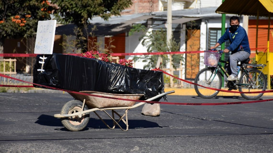 A coffin wrapped in plastic containing the remains of an unidentified men, who died last week, sits on a wheelbarrow in the middle of a street, placed there by his family to draw attention of the authorities to show that his remains are yet to be collected, in Cochabamba, Bolivia, Saturday, July 4, 2020.