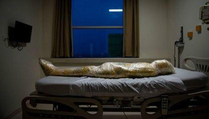 El cuerpo de una presunta víctima de Covid-19 yace en un hospital indonesio. Después de la muerte del paciente, las enfermeras del hospital envolvieron el cuerpo inerte en capas de plástico y aplicaron desinfectante para evitar la propagación del virus.