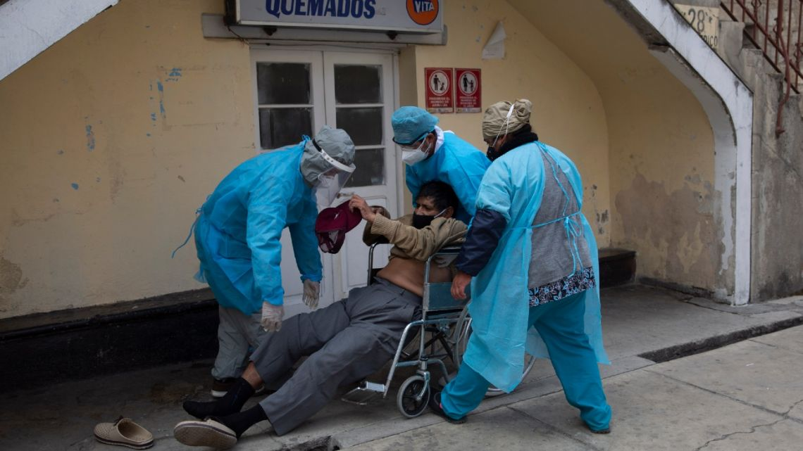 Healthcare workers lift a man who was lying on the ground outside the General Hospital into a wheelchair to be taken to the emergency room that treats people suspected of having Covid-19 in La Paz, Bolivia, Thursday, July 23, 2020.
