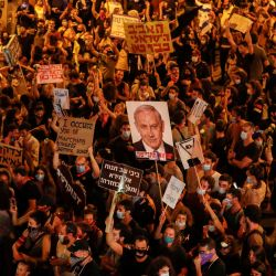 Los manifestantes sostienen pancartas durante una manifestación contra el primer ministro israelí frente a su residencia oficial en Jerusalén. | Foto:AHMAD GHARABLI / AFP