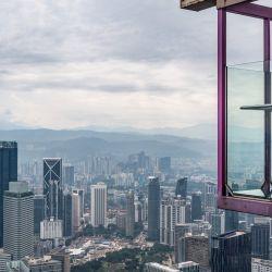 Una mujer posa para una foto, con la vista de la ciudad al fondo, desde el Sky Box en la Torre KL en Kuala Lumpur. | Foto:Mohd Rasfan / AFP