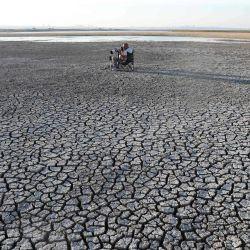 Un fotógrafo toma fotos del suelo agrietado después de una sequía en el estanque Dikilitas en el distrito Golbasi de Ankara. | Foto:Adem Altan / AFP