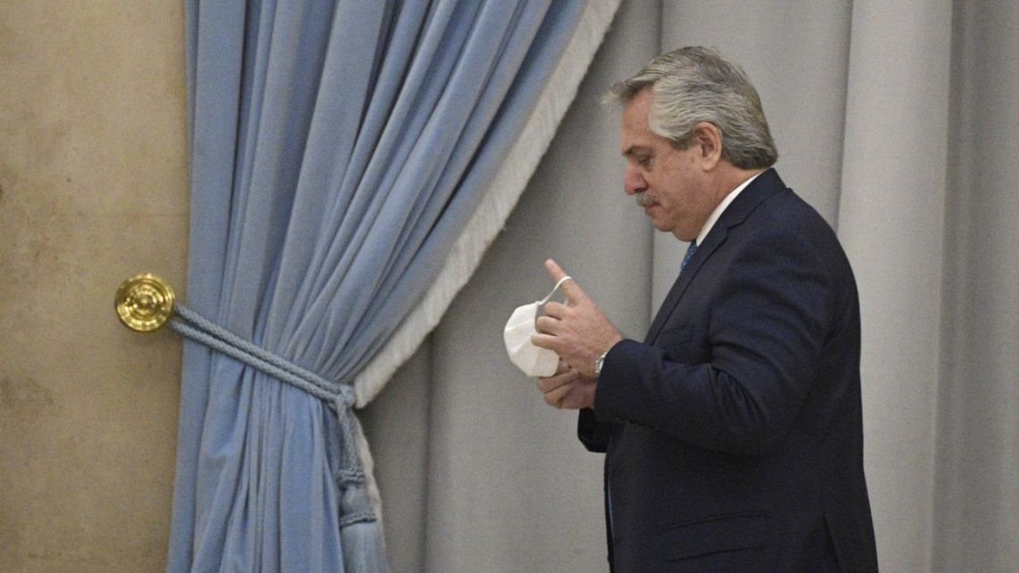 President Alberto Fernández takes off his face mask before delivering a speech in Buenos Aires on July 22, 2020.