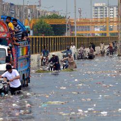 La gente camina por una calle inundada después de fuertes lluvias monzónicas en Karachi.   Foto:Rizwan Tabassum / AFP
