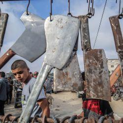 Un joven palestino mira un puesto de cuchillos en un mercado de ganado en la ciudad de Rafah, en el sur de la Franja de Gaza, mientras los musulmanes se preparan para el sacrificio de la fiesta de Eid al-Adha (Festival del Sacrificio).   Foto:SAID KHATIB / AFP