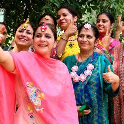 Los profesores universitarios toman fotos selfie durante el festival Teej para conmemorar el mes de Sawan (lluvia) en el Khalsa College for Women en Amritsar. | Foto:NARINDER NANU / AFP