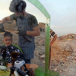 Un niño iraquí se corta el pelo entre los escombros en la ciudad norteña de Mosul antes de la fiesta musulmana de Eid al-Adha.   Foto:Zaid AL-Obeidi / AFP
