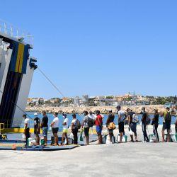 Migrantes escoltados por la policía de Guardia Di finanza hacen cola para abordar un ferry turístico a Porto Empedocle en la isla italiana de Pelagie de Lampedusa. - Los barcos con migrantes principalmente de Túnez continúan llegando a la isla italiana de Lampedusa.  | Foto:Alberto Pizzoli / AFP