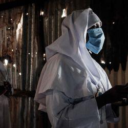 Los fieles de Legio Maria con máscaras protectoras asisten a una oración en su iglesia en el barrio marginal de Kibera de Nairobi, después de que el presidente de Kenia permitiera que los lugares de culto reabrieran bajo estrictas pautas para frenar la propagación del nuevo coronavirus (COVID- 19. | Foto:Yasuyoshi Chiba / AFP