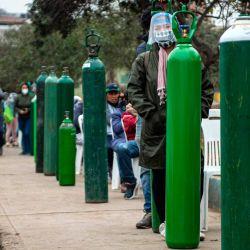 Familiares de pacientes de COVID-19 hacen cola para recargar cilindros de oxígeno en Villa María del Triunfo, en las afueras del sur de Lima. | Foto:Ernesto Benavides / AFP