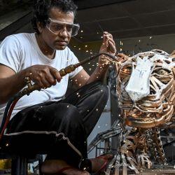 El artesano Lalith Senannnayake suelda chatarra de metal para hacer una escultura en forma de leopardo en su casa de Wattala, cerca de Colombo.   Foto:Ishara S. Kodikara / AFP