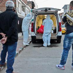 Vecinos y familiares miran cómo los trabajadores funerarios colocan el cadáver de un hombre que presuntamente murió de COVID-19 en su casa, en una camioneta, en Cali, Colombia. | Foto:Luis Robayo / AFP