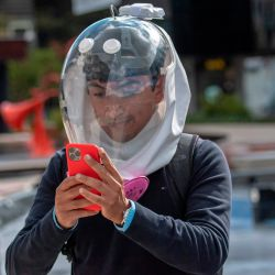 El diseñador industrial colombiano Ricardo Conde usa una nueva máscara de ventilación contra la propagación del nuevo coronavirus diseñado por él junto con un médico y dos ingenieros aeronáuticos, ya que usa un teléfono móvil en Bogotá. | Foto:Juan Barreto / AFP
