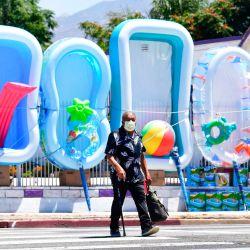 Un hombre usa una máscara facial al pasar frente a una exhibición de artículos acuáticos y de piscinas para la venta en Pacoima, California. | Foto:Frederic J. Brown / AFP