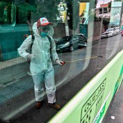 Un trabajador de limpieza con equipo de protección personal (PPE) se refleja en una ventana mientras desinfecta una camioneta de transporte público en la Ciudad de México, en medio de la nueva pandemia de coronavirus. | Foto:PEDRO PARDO / AFP