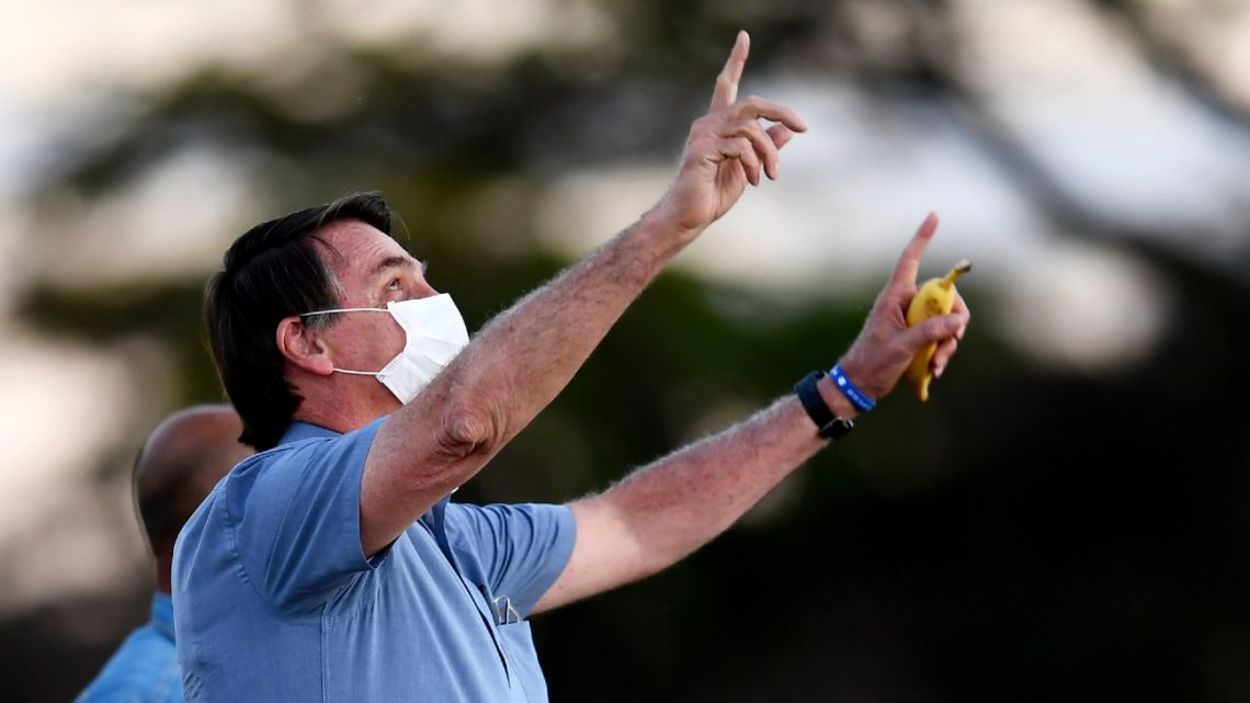 Brazilian President Jair Bolsonaro gestures as he speaks to supporters while holding a banana in the garden of the Alvorada Palace in Brasilia, on July 24, 2020.
