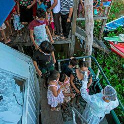Un trabajador de salud de la Unidad de Buques de Atención Médica UBS verifica la temperatura corporal de un paciente en la comunidad ribereña de Selma Barra, en el río Buissu, municipio de Melgaco en la isla de Marajo, estado de Pará, Brasil. | Foto:TARSO SARRAF / AFP