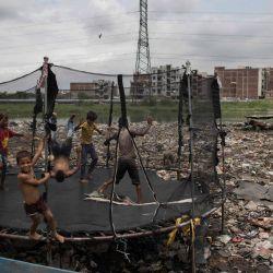 Los niños saltan en un trampolín en un vertedero en un barrio residencial de Nueva Delhi.   Foto:Xavier Galiana / AFP