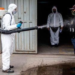 Un trabajador municipal desinfecta a un guardia de seguridad en Villa María del Triunfo, en las afueras del sur de Lima.   Foto:ERNESTO BENAVIDES / AFP