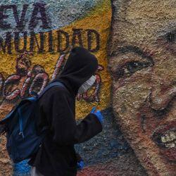 Un hombre con máscaras y guantes protectores pasa junto a un mural que representa al fallecido presidente de Venezuela, Hugo Chávez, en el barrio de La Vega en Caracas.   Foto:Federico Parra / AFP