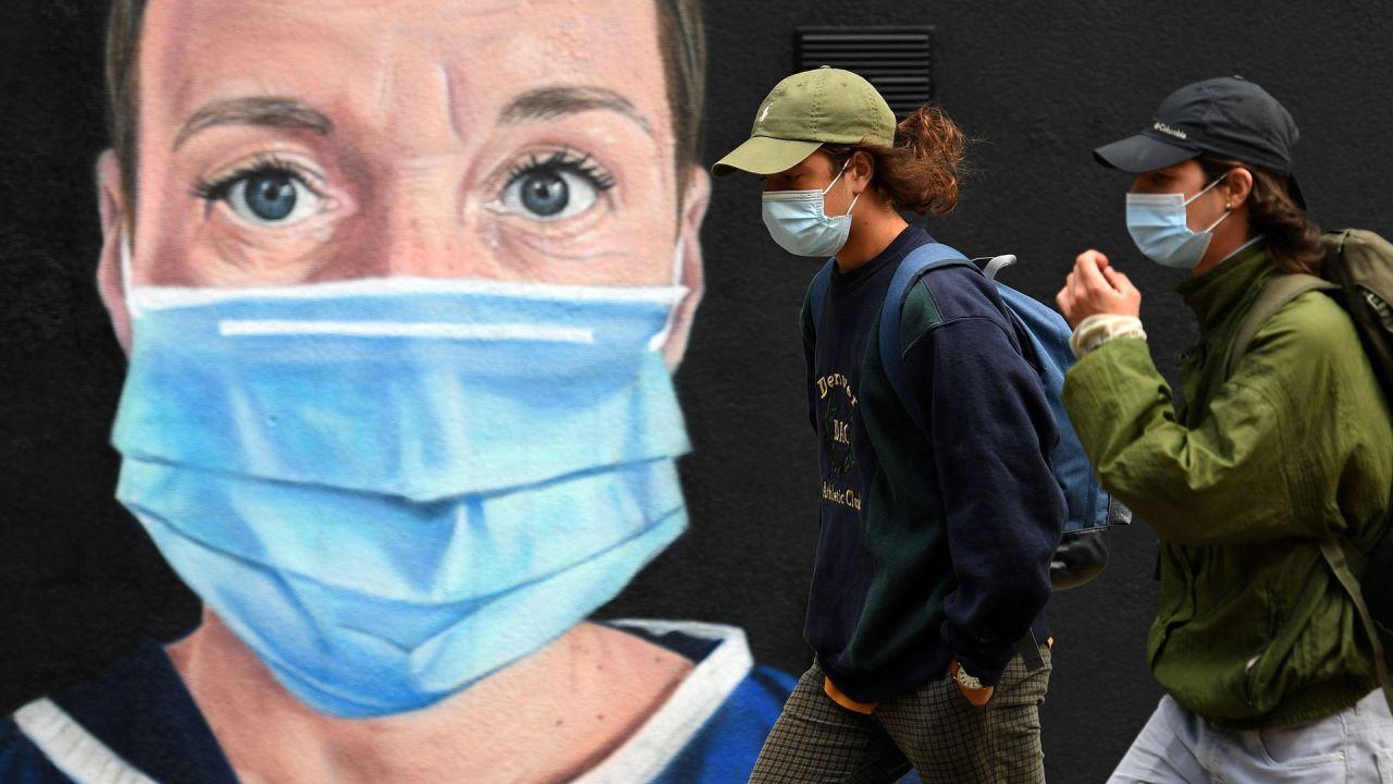 Los peatones que usan una máscara facial o una cobertura debido a la pandemia de COVID-19, pasan por los graffitis del artista @ akse_p19, que representan a una enfermera con matorrales y una máscara facial, pero con un halo de Ángel sobre su cabeza, en Manchester, noroeste de Inglaterra. | Foto:OLI SCARFF / AFP
