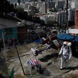 Un voluntario desinfecta un área de la azotea dentro de Santa Marta Favela, en Río de Janeiro, Brasil, durante la pandemia de COVID-19. | Foto:CARL DE SOUZA / AFP