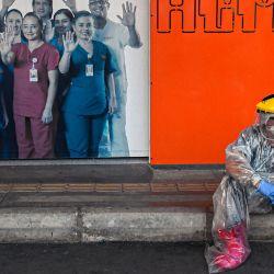 Un trabajador de la salud tomando un descanso frente al Hospital General de Medellín, en medio de la pandemia COVID-19, en Medellín. | Foto:JOAQUIN SARMIENTO / AFP