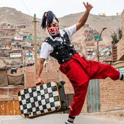 Un payaso con máscara facial poa para una foto antes de actuar en el distrito de Puente Piedra, en las afueras del norte de Lima, durante la pandemia de COVID-19.  | Foto:Ernesto Benavides / AFP