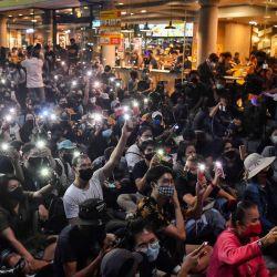Los manifestantes usan teléfonos móviles como linternas mientras cantan para protestar canciones durante una manifestación antigubernamental con temática de Harry Potter en el Monumento a la Democracia en Bangkok. | Foto:LILLIAN SUWANRUMPHA / AFP