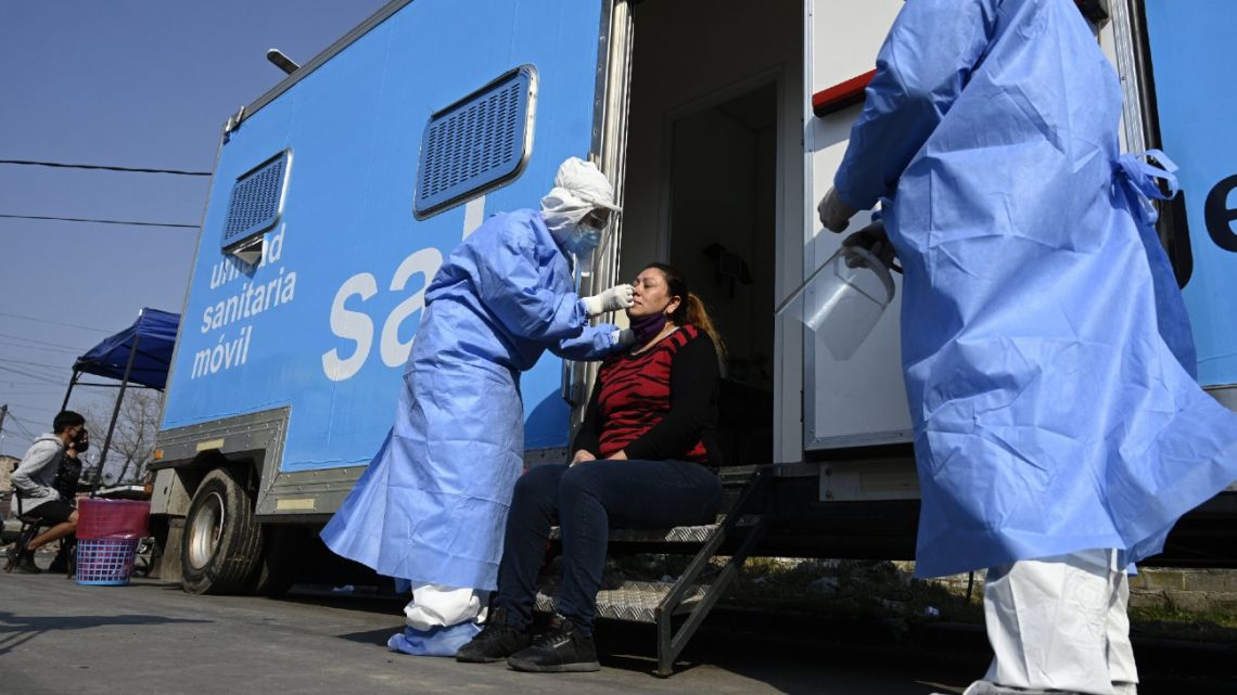 A doctor takes samples for a PCR test to a woman with Covid-19 symptoms at a mobile health unit in Villa Fiorito, Buenos Aires Province.