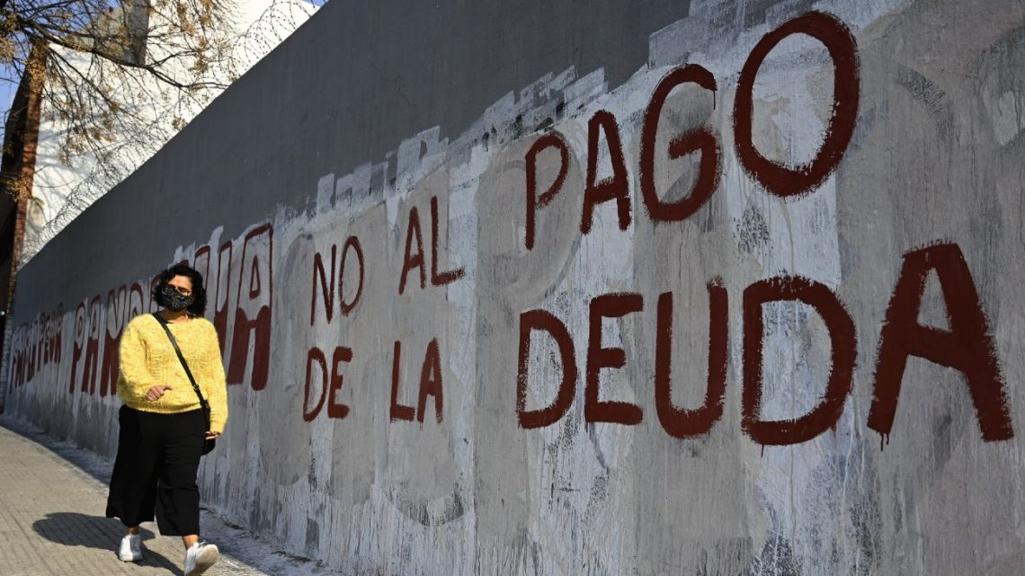 A woman passes by a wall with a anti-debt payment slogan in Buenos Aires, on August 3, 2020.
