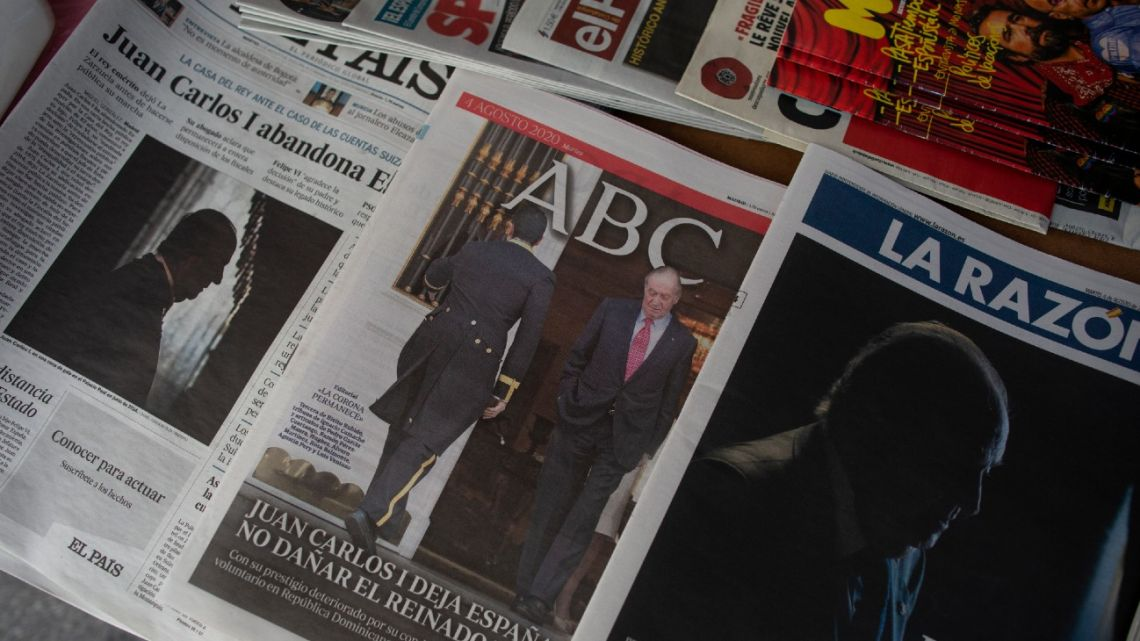 Front pages of newspapers are displayed with the news on Spain's former monarch, King Juan Carlos I, in Madrid, Spain, Tuesday, August  4, 2020. Speculation over the whereabouts of former monarch Juan Carlos is gripping Spain, a day after he announced he was leaving the country for an unspecified destination amid a growing financial scandal.