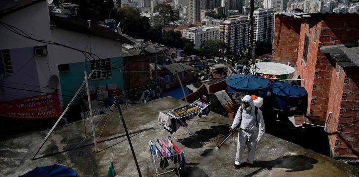 Un voluntario desinfecta un área de la azotea dentro de Santa Marta Favela, en Río de Janeiro, Brasil, durante la pandemia de COVID-19.