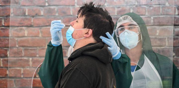 Un biólogo del Institut Pasteur de Lille toma una muestra de un hisopo de un hombre que está probando el nuevo coronavirus COVID-19 en Lille, norte de Francia, ya que la ciudad de Lille, un bullicioso centro cerca de la frontera belga, ha sido objeto de especial preocupación. con la prevalencia del virus duplicando a 38 personas por 100,000 en solo dos semanas.