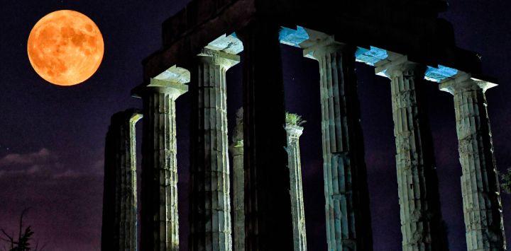 La luna llena se eleva detrás del antiguo templo de Zeus en Nemea.