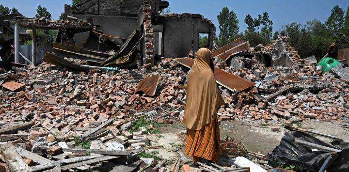 Una mujer inspecciona los escombros de las casas de sus familiares que fueron arrojados por morteros disparados por soldados indios durante un tiroteo con rebeldes, en Sopore, al norte de Srinagar.