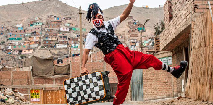 Un payaso con máscara facial poa para una foto antes de actuar en el distrito de Puente Piedra, en las afueras del norte de Lima, durante la pandemia de COVID-19.