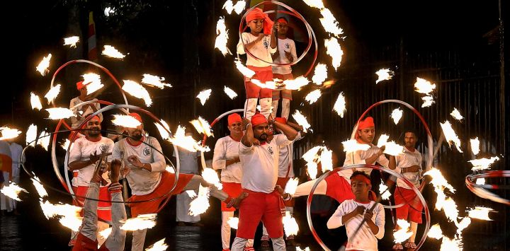 Los bailarines de fuego actúan frente al histórico Templo Budista del Diente, mientras participan en una procesión durante el festival Esala Perahera en la antigua capital de la colina de Kandy, a unos 116 km de Colombo.