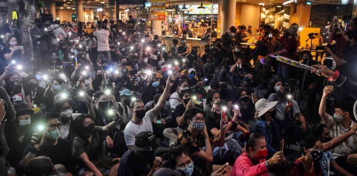 Los manifestantes usan teléfonos móviles como linternas mientras cantan para protestar canciones durante una manifestación antigubernamental con temática de Harry Potter en el Monumento a la Democracia en Bangkok.