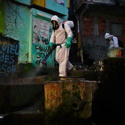 Un voluntario desinfecta un área dentro de la Favela de Santa Marta, en Río de Janeiro, Brasil, durante la pandemia COVID-19.   Foto:CARL DE SOUZA / AFP